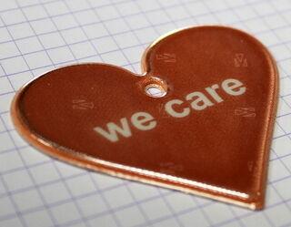 WE CARE - punane südamekujuline helkur.